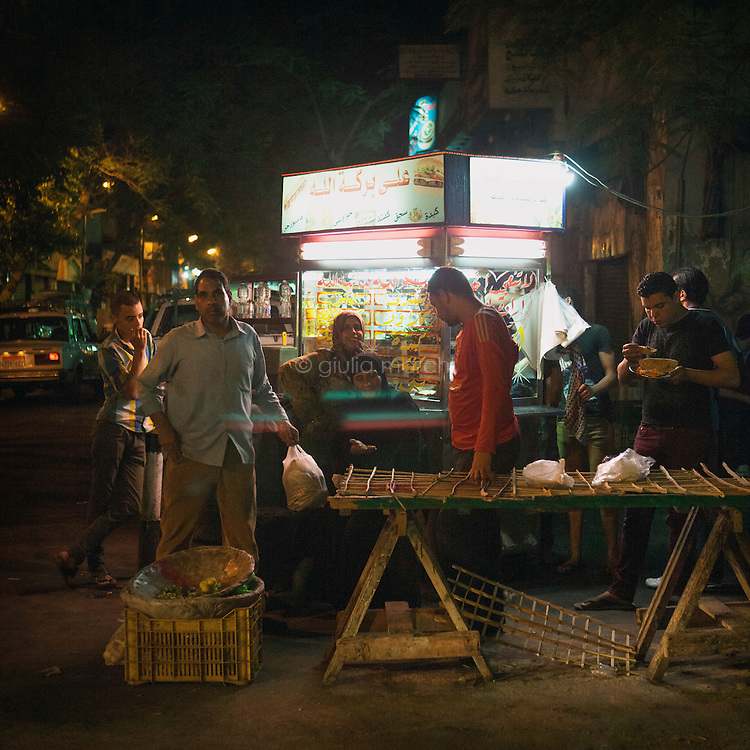 Egypt / Cairo / 20.5.2013 / Street scene in Downtown Cairo: in front of a food cart some people stand eating, some other buy bread, some other talk.