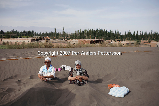 """TURPAN, CHINA - JUNE 10: A man and his wife rest in the sand as they are having therapy at a """"Sand Therapy Center"""", on June 10, 2007, about 10 kilometers outside Turpan, China. They are both suffering from pain in their legs and only this therapy eases the pain for them. Sand Therapy is an important part of Uygur traditional medicine and many people come every year to get healed from different ailments, including hypertension, pain, and rheumatism. It's only open in June and July every year and thousands of patients from around China during the hottest season, that's the only time when it is hot enough. Most of the people stay in the nearby center where they can have special baths and massages. (Photo by Per-Anders Pettersson)..."""