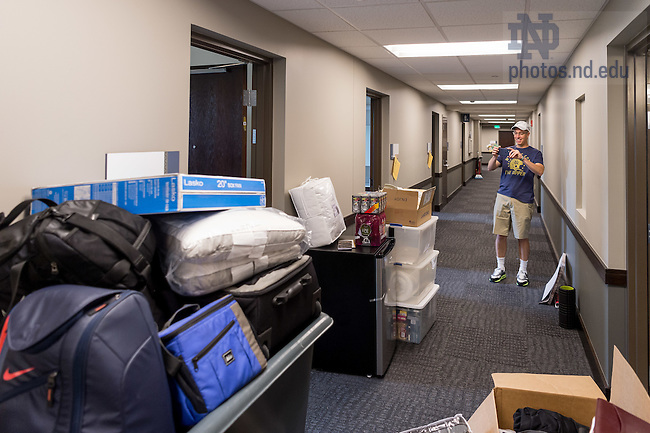 """August 19, 2016; Jerry Quinn '89 takes a photo of the supplies his son Patrick brought to his Dunne Hall dorm room for move-in day of Welcome Weekend 2016. A former Morrissey Manor resident, Jerry was impressed with Notre Dame's newest men's residence hall. """"This isn't a dorm, it's a hotel,"""" he said. (Photo by Matt Cashore/University of Notre Dame)"""