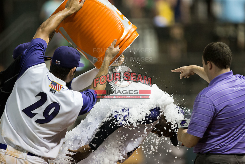 Keon Barnum (center) of the Winston-Salem Dash is doused with a bucket of ice by teammates Nick Basto (29) and Jordan Guerrero (23) as after Barnum scored the winning run on a wild pitch in the bottom of the ninth inning against the Myrtle Beach Pelicans at BB&T Ballpark on August 20, 2015 in Winston-Salem, North Carolina.  (Brian Westerholt/Four Seam Images)