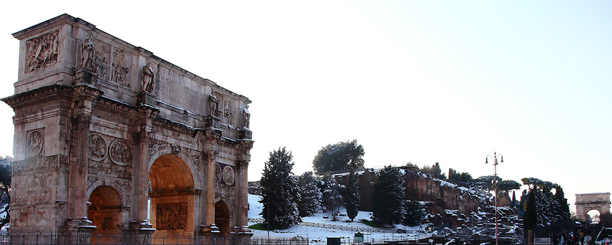 Rome, Fora: A peculiar view of the Arc of Costantino (in foreground, on the left) and of the Arc of Tito (on the background, on the right), in a snow-clad frame, with in particular the ancient ruins, the trees and the lawn among them covered by snow. The photo is taken in the late afternoon, after a snowing night (February, 2012).  This is an enlargement of a part of the original photo.<br />