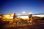 Panning shot of cyclists by Tirana Bridge, Seville, Spain