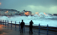 Pictured: Two amateur photographers taking pictures of tuge waves crashing against the promenade wall in Porthcawl, south Wales. Friday 03 January 2014<br /> Re: Flood warnings have been issued  by the Environment Agency due to strong winds and high tides for part of the UK.