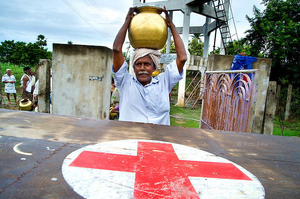 Villagers make use of a Red Cross water purifying station in a small village in Krishna district, Andhra Pradesh, which recently suffered one of the worst floods in 100 years.<br /> <br /> Nearly 400 people died in this district and neighbouring Karnataka, and more than 500,000 were displaced.