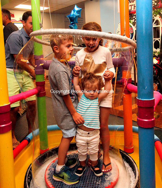 TORRINGTON, CT - 08 AUGUST 2017 - 080517JW02.jpg -- Jake Rossi age 7 with sisters Anna Rossi age 8 and Lyla Rossi age 1, hold together as their father John Rossi creates a soap bubble around them during the KidsPlay Children's Museum 5th anniversary Saturday morning.  Jonathan Wilcox Republican-American
