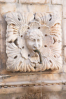 the Grand Big Onofrio fountain velika Onofrijeva, detail of a carved stone head with spout Placa Stradun Dubrovnik, old city. Dalmatian Coast, Croatia, Europe.