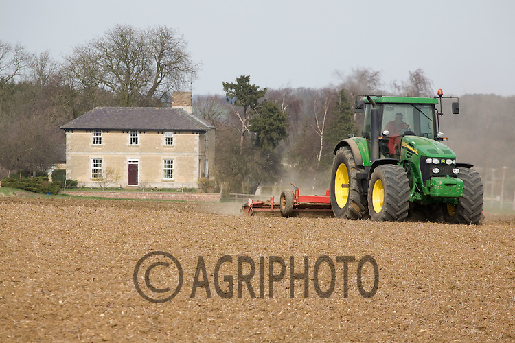 Tractor working on land in front off a farmhouse