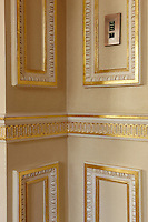 A corner of a room with ornate gilded plasterwork.