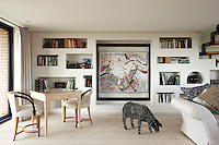 The recessed storage along the full length of the room provides both easy access to books, and a place to display artwork