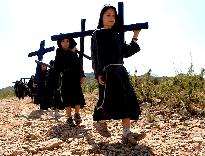IRUNBERRI - LUMBIER, NAVARRE JUNE 11: Children dressed in black monks habits carry heavy crosses during the celebration of the 'Cruceros' brotherhood penitential pilgrimage to the 'Ermita de la Trinidad' on June 11, 2006 in Irunberri - Lumbier, Navarre. Photo by Ander Gillenea