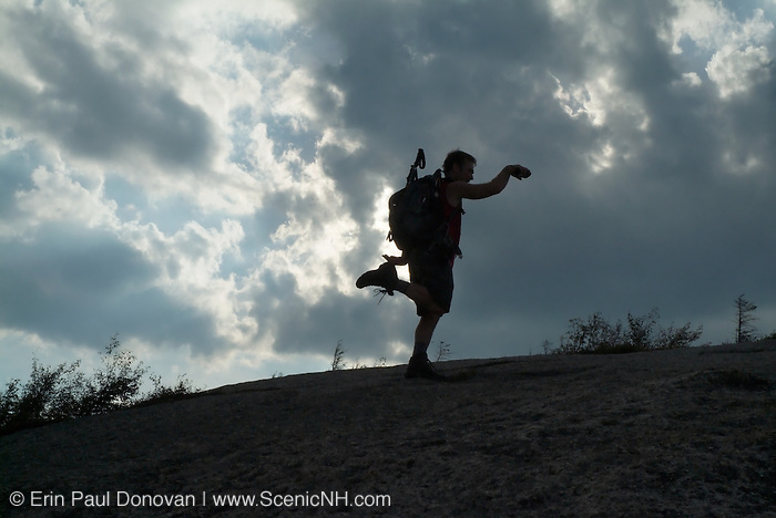 The silhouette of a hiker on the summit of Middle Sugarloaf Mountain at sunset during the summer months in the scenic landscape of the White Mountains, New Hampshire USA .