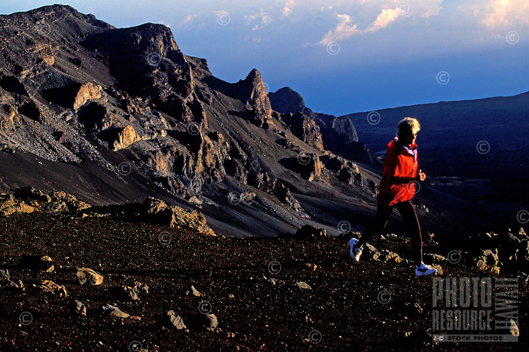 A woman running on the lava fields in Haleakala national park
