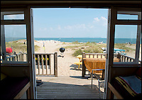 BNPS.co.uk (01202 558833)<br /> Pic: LauraDale/BNPS<br /> <br /> The beautiful sea view from inside the property.<br /> <br /> A modest beach hut with no bathroom or mains electricity has gone on the market for a whopping 270,000 pounds - making it the most expensive in Britain.<br /> <br /> The asking price for the tiny wooden shack on Mudeford Spit near Christchurch, Dorset, is the same cost as a plush three-bedroom house in some parts of the country and is as much as a top-of-the-range Ferrari car.<br /> <br /> The 18ft by 12ft hut can sleep up to 12 people - four people on a mezzanine deck, four on two sofa beds and another two on a pull-out bed.<br /> <br /> The huge asking price is because it is just a stones throw away from the water boasting stunning sea views out towards the Isle of Wight and the Needles.<br /> <br /> The current owners are selling the beach hut so that they can move to another one on the same sandy strip with a different view.