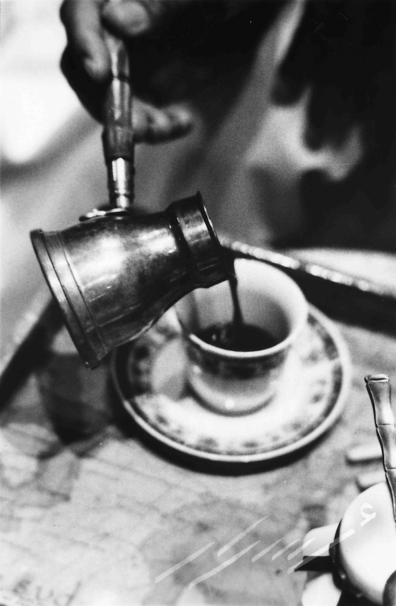 Arabian man's hand pouring Turkish coffee in a Turkish coffee cup.