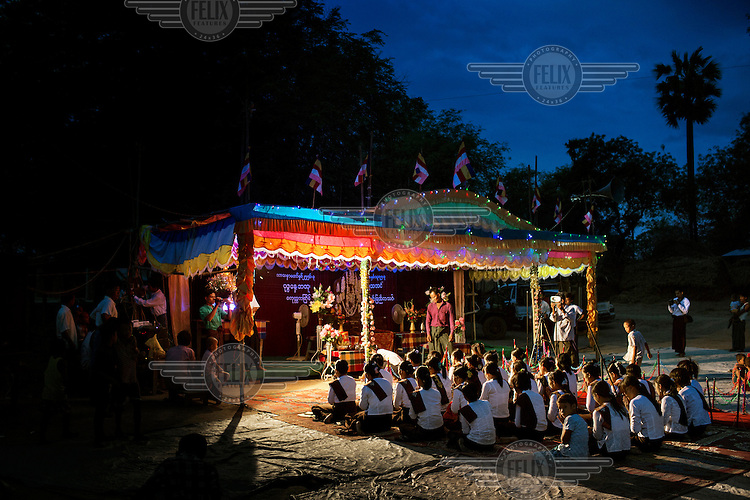 Villagers from Kyaw Min chant and pray as they wait for U Wirathu, the spiritual leader of the Buddhist nationalist 969 Movement, to give a sermon at the Shwe Areleain Monastery in Kyaw Min Village, Myiamu Township. U Wirathu is an abbot in the New Maesoeyin Monastery where he leads about 60 monks and has influence over more than 2,500 residing there. He travels the country giving sermons to religious and laypeople encouraging Buddhists to shun Muslim business and communities. /Felix Features