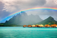 Bungalows over water with rainbow and Mt. Otemanu. Bora Bora. French Polynesia