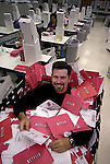 Netflix Chief Executive Officer Reed Hastings sits in a mail delivery case of thousands of DVDs at their distribution plant in San Jose, Calif., Monday, Sept. 10, 2001. Online DVD rental company Netflix is emerging as one of the Internet's rising stars that has attracted a cast of 300,000 subscribers who pay a $19.95 monthly fee to get up to three DVD rentals mailed to them. (AP Photo/Paul Sakuma)
