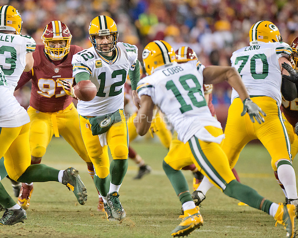 Green Bay Packers quarterback Aaron Rodgers (12) hands off to Green wide receiver Randall Cobb (18) in third quarter action against the Washington Redskins in an NFC Wild Card game at FedEx Field in Landover, Maryland on Sunday, January 10, 2016.  The Packers won the game 35 - 18.<br /> Credit: Ron Sachs / CNP/MediaPunch ***FOR EDITORIAL USE ONLY***