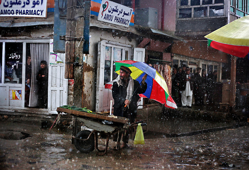 A vegetable vendor takes refuge from a sudden rainstorm at the bazaar in Faizabad. ..Badakhshan province, Afghanistan.