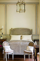This bedroom is furnished in the French style with a pair of Louis XVI chairs and a cane bed