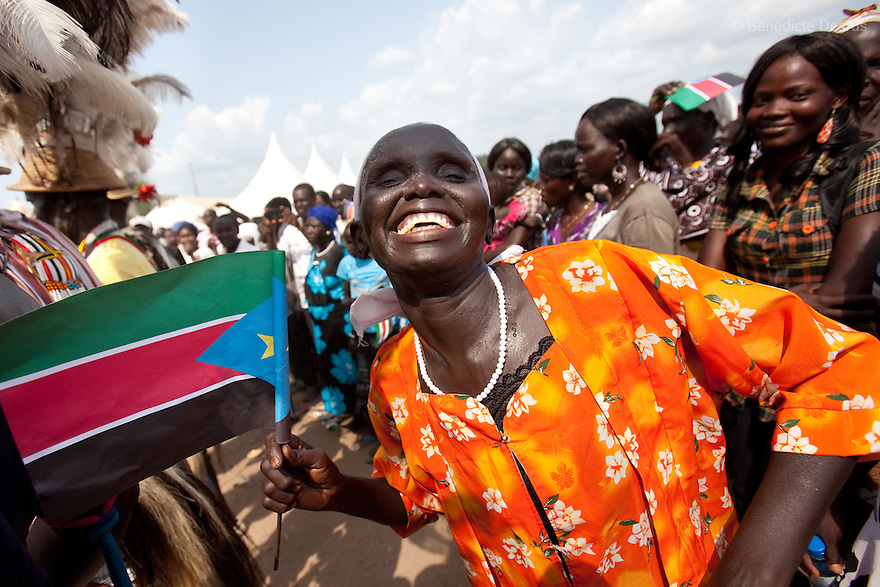 Saturday 9 july 2011 - Juba, Republic of South Sudan - A South Sudanese woman waves the flag of her new country and dances during South Sudan's independence day celebrations in Juba. Tens of thousands of citizens of the new South Sudan celebrate national independence but whether statehood will resolve issues of identity after a decades-long war remains to be seen. Photo credit: Benedicte Desrus