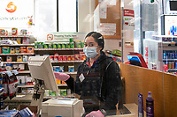 New York, New York City, during the time of the Coronavirus. Woman working behind the counter at CVS pharmacy is protected by wearing a  mask, gloves and plexiglasss.