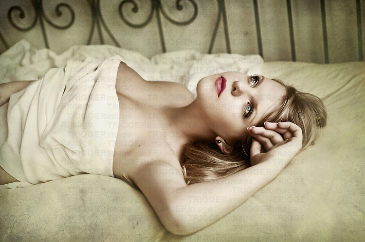 Close up of young woman with blonde hair lying on a bed gazing thoughtfully