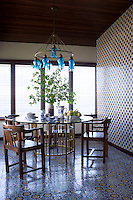 The floor and wall of the breakfast room are covered in Moroccan-style ceramic mosaic tiles while an antique Egyptian chandelier hangs from the ceiling