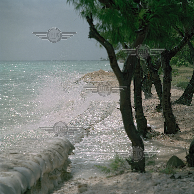 A sea wall is taken over by high tide and increasingly high sea levels. The situation is worsened by the building of a causeway linking islets together causing a change to the natural currents.