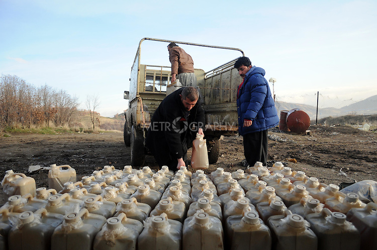 BASHMAKH, IRAQ:  Iraqi Kurds unload cheap petrol trafficked from Iran...Iranian Kurdish smugglers traffic petrol from Iran into Iraq and alcohol from Iraq into Iran.  On foot, a smuggler can look to make around $10 per trip whereas with a horse a smuggler can make $100.  The routes are very dangerous with the risk of stepping on land mines or  being shot by the Iranian military..Photo by Kamaran Najm/Metrography