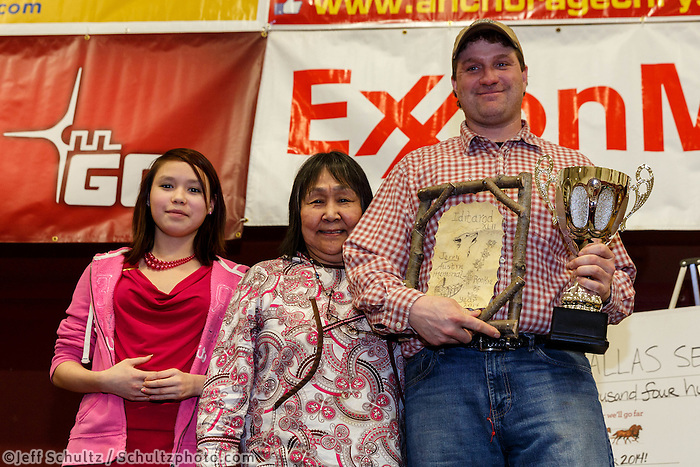 Clara Austin presents Nathan Schroeder with the Jerry Austin Rookie of the year award at the musher 's finishers banquet in Nome on Sunday March 16 after the 2014 Iditarod Sled Dog Race.<br /> <br /> PHOTO (c) BY JEFF SCHULTZ/IditarodPhotos.com -- REPRODUCTION PROHIBITED WITHOUT PERMISSION