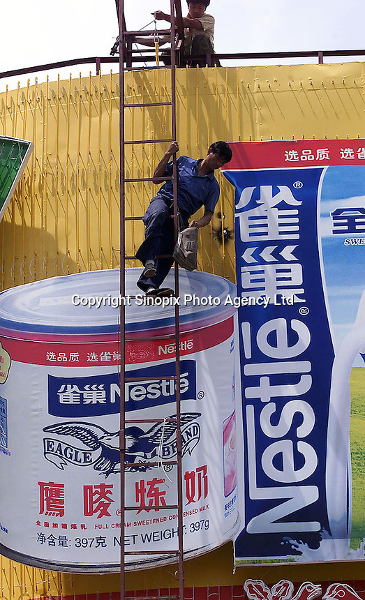 Workers put up the Nestlé advertising billboard in Beijing, China..29-MAY-02