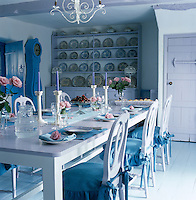 Blue and white china, a blue Mora clock and blue cushions on the Swedish-style dining chairs punctuate this lilac-painted kitchen