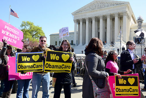 Demonstrators outside the United States Supreme Court Building as oral arguments concerning the Constitutionality of the U.S. Health Care Law continue inside the building.  .Credit: Ron Sachs / CNP