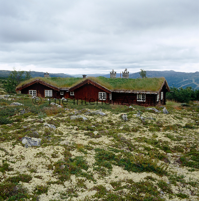 The outside walls of this Norwegian cabin are protected by a durable coat of tar and the roof is covered with grass which blends it into the landscape and acts as a natural form of central heating