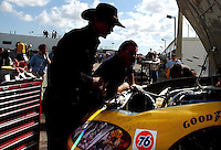 Racing Legend Richard Petty wearing his signature hat, looks under the hood and into the engine compartment of the race car he owns and driven by John Andretti in the garage area at Daytona International Speedway.