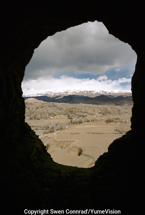 A view on the ruins Shahr i Gholghola citadel in the valley of Bamiyan, from a niche on the top head of the 6 meters Kakrak Buddha statue in 1996..In the Kakrak Valley, 2 kilometres south of the giant Bamiyan Buddha cliff , there is a 6 meters standing Buddha in a niche which was discovered in 1930. The Buddha niche is also surrounded by caves but the paintings were painstakingly removed by French archaeologists..Some scholars consider these mystic diagrams from Kakrak to be the earliest specimens of the type of cosmic Mandala found today in Nepal and Tibet.