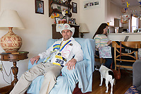 "Carlos Arredondo, 57, (left) and his wife Melida Arredondo, 52, are seen in their home in Roslindale, Boston, Massachusetts, USA, on Sat., March 31, 2018. Arredondo is well known as the ""man in the cowboy hat"" who helped out in the aftermath of the Boston Marathon Bombing in 2013. Carlos is wearing a jacket that he has used to create a t-shirt design for when he runs the Boston Marathon later this year. Though he has run the race unofficially previously, this will be the first time he runs it ""legally,"" he says. Their dog, Buddy, age 18, can be seen on the floor. Carlos says he often accidentally calls Buddy by his son's name, Brian. Brian Arredondo, who can be seen in the photo on the wall above Carlos at left, died by suicide in 2011 after a battle with depression following the 2004 death of Arrendondo's other son  Marine Lance Corporal Alexander Scott Arredondo, who was killed while serving in Iraq."
