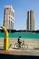 "Milano, quartiere Garibaldi, progetto di riqualificazione dell'area di Porta Nuova. Una donna in bicicletta, una colonnina per taxi e le Torri Garibaldi --- Milan, Garibaldi district,  requalification project of ""Porta Nuova"" area. A woman on a bicycle, a taxi column and the skyscrapers ""Torri Garibaldi"""