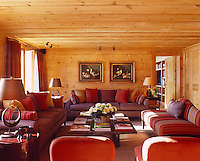 The chalet living room is furnished with comfortable sofas and cushions in red and purple tones