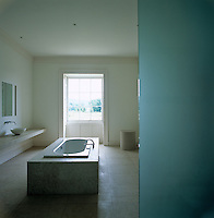 A large white marble bath on a limestone floor is enclosed within panels of opaque blue glass