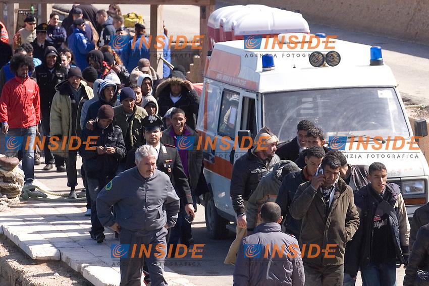 I trentadue profughi provenienti dalla Tunisia vengono accompagnati all autobus per essere portati al Centro di Accoglienza e Primo Soccorso di Lampedusa...Lampedusa 05 Marzo 2011...Photo Serena Cremaschi Insidefoto..........