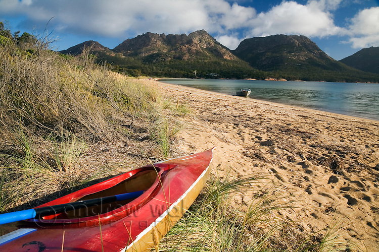 Kayak on the shores of Coles Bay, with The Hazards mountain peaks beyond.  Freycinet National Park, Tasmania, Australia