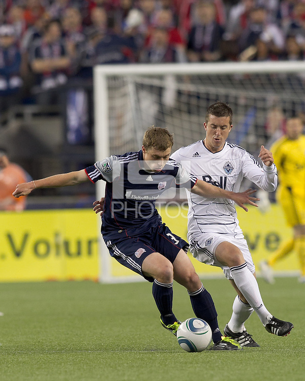 New England Revolution midfielder Zak Boggs (33) dribbles as Vancouver Whitecaps FC midfielder Jeb Brovsky (12) defends. In a Major League Soccer (MLS) match, the New England Revolution defeated the Vancouver Whitecaps FC, 1-0, at Gillette Stadium on May14, 2011.