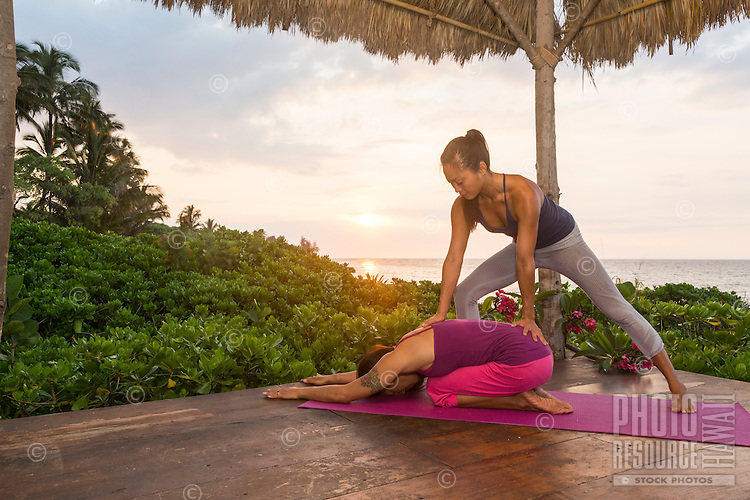 Yoga instructor Miki Sato assists a student with the child's pose yoga asana on a beach in Hawai'i.