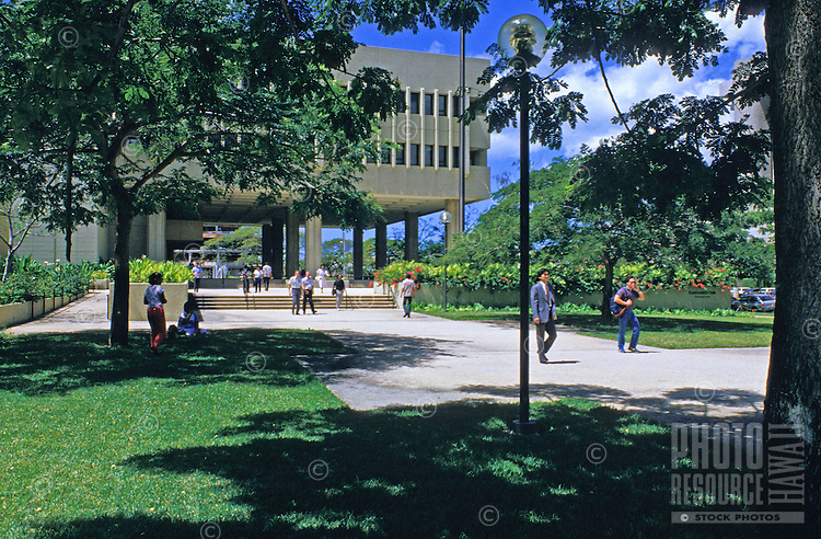 Engaging in city life, people make their way in a green area of downtown Honolulu