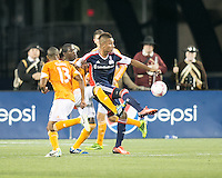 New England Revolution forward Juan Agudelo (10) controls the ball as Houston Dynamo midfielder Ricardo Clark (13), Houston Dynamo defender Kofi Sarkodie (8) and Houston Dynamo defender Bobby Boswell (32) move in.  The New England Revolution played to a 1-1 draw against the Houston Dynamo during a Major League Soccer (MLS) match at Gillette Stadium in Foxborough, MA on September 28, 2013.
