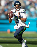 CHARLOTTE, NC - DECEMBER 15: Russell Wilson #3 of the Seattle Seahawks looks for a receiver during a game between Seattle Seahawks and Carolina Panthers at Bank of America Stadium on December 15, 2019 in Charlotte, North Carolina.