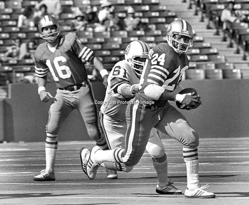 San Francisco 49ers Delvin Williams chased by Tampa Bay Bucs #61 Dewey Selmon, QB Jim Plunkett. (1977 photo/Ron Riesterer)