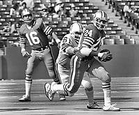 San Francisco 49ers Delvin Williams chased by Tampa Bay Bucs #61 Dewey Selmon, QB Jim Plunkett. (1977 photo/Ron Riesterer)